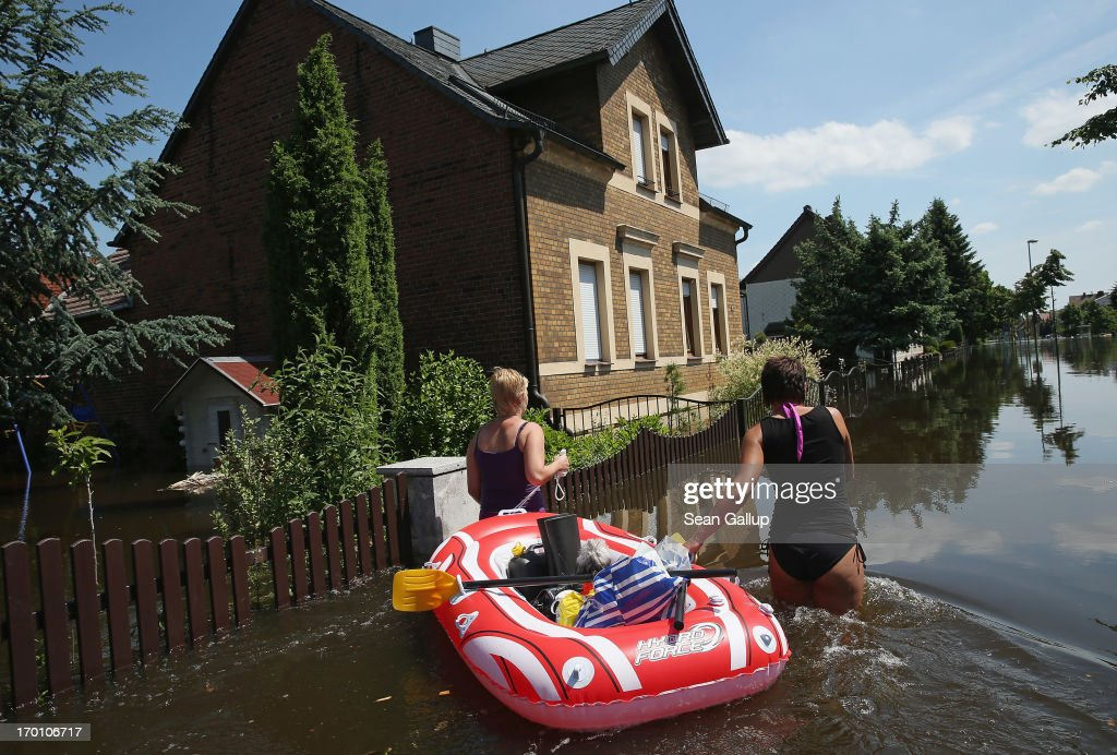 Friends Stephanie (R) and Sandra transport Stephanie's dog Chewbaca, groceries and bottles of butane in a rubber raft through a flooded street to Sandra's home near the swollen Elbe river on June 7, 2013 in Elster, Germany. Floodwaters that have devastated parts of Saxony and Thuringia are now moving north, threatening towns along the Elbe and Saale rivers all the way to Hamburg. Eastern and southern Germany are suffering under floods that in some cases are the worst in 400 years. At least four people are dead and tens of thousands have evacuated their homes.