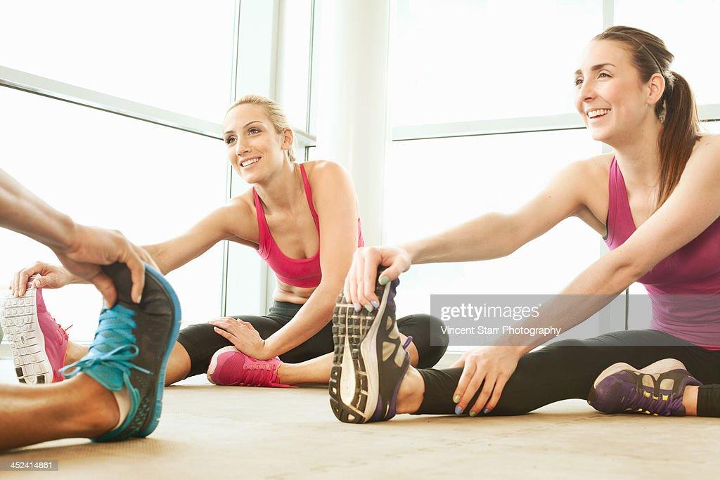 Friends stretching in gymnasium