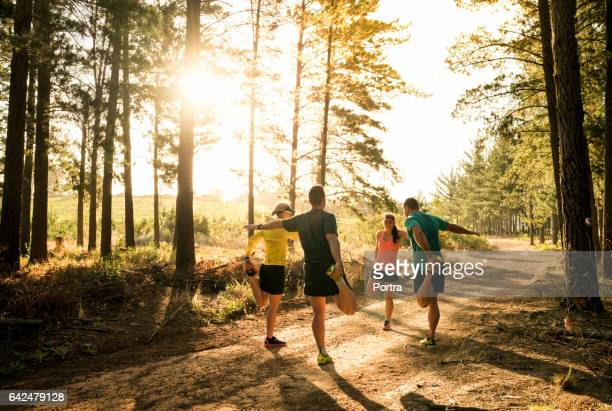 Friends stretching legs before jogging on road