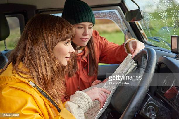 Friends studying map in car