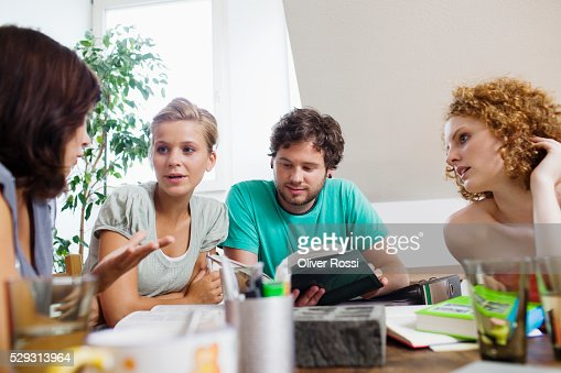 Friends studying together at table : Foto stock