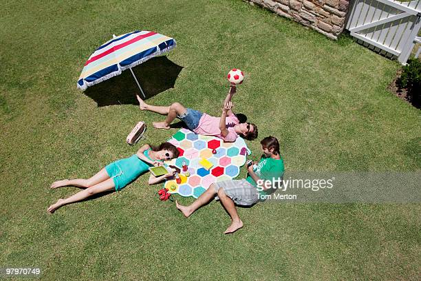 Friends sunbathing and relaxing on sunny grass