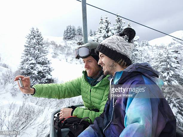 Friends take picture of themselves on a ski lift.