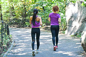 Two young women take a jog in a park during a beautiful spring day