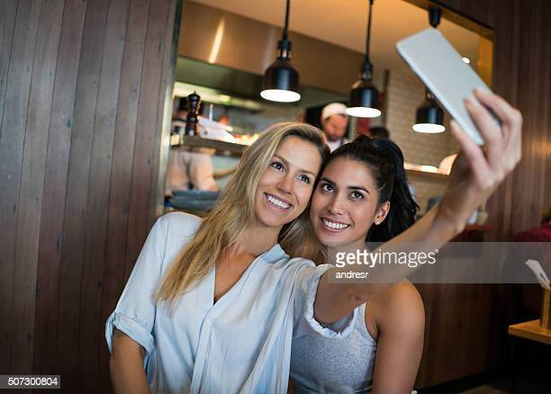 Friends taking a selfie at a cafe