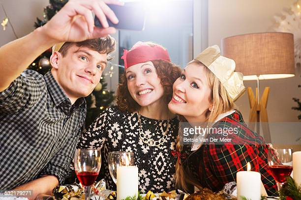 Friends taking a Selfie at Christmas dinner table.