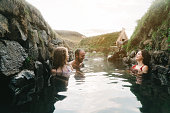 Young Caucasian friends taking bath in hot spring in Iceland