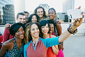 Friends taking cell phone selfie on urban rooftop