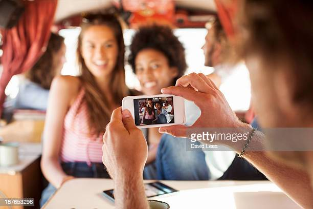 Friends taking photo of themselves in camper van