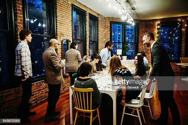 Friends taking seats at table for dinner party