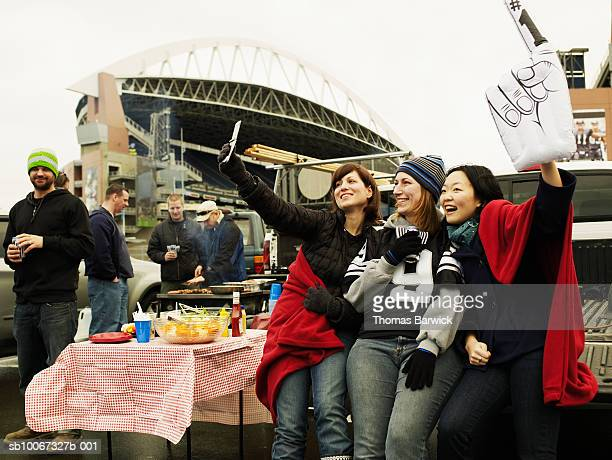 Friends taking self photograph at tailgate party