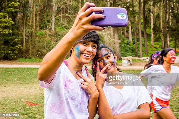 Friends taking selfie covered in pigment powder