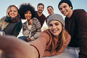 Young friends taking selfie during beach party. Group of mixed race  friends taking selfie on the seashore.