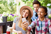Multi-ethnic group of three  happy young people taking smartphone selfie in outdoor cafe making faces to camera