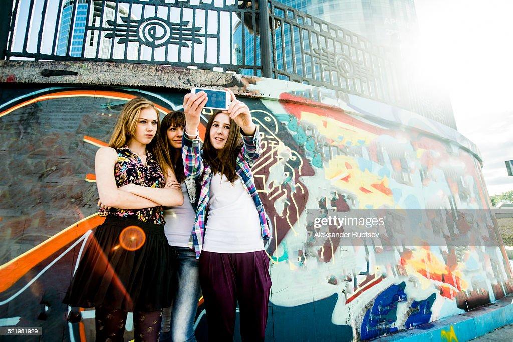 Friends taking selfie, mural in background