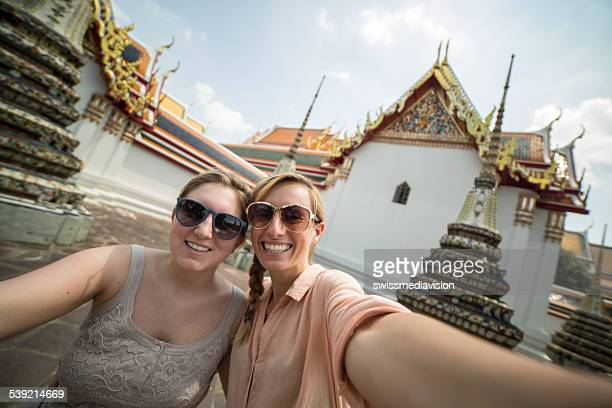 Friends taking selfie near Thai temples