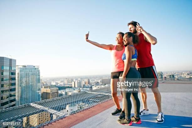 Friends taking selfie on urban rooftop