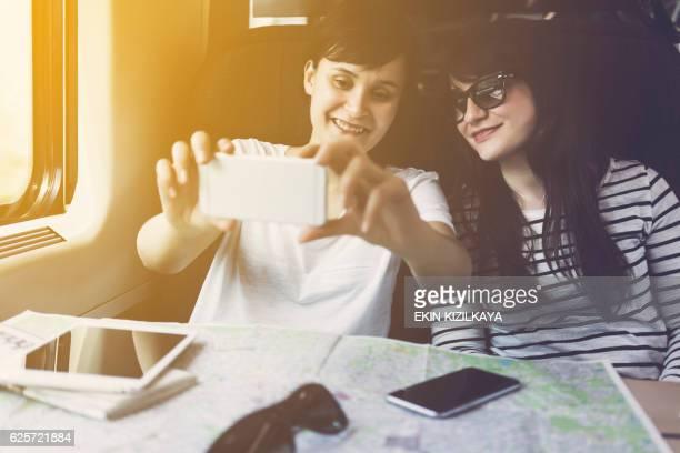 Friends taking selfie, travelling in a train