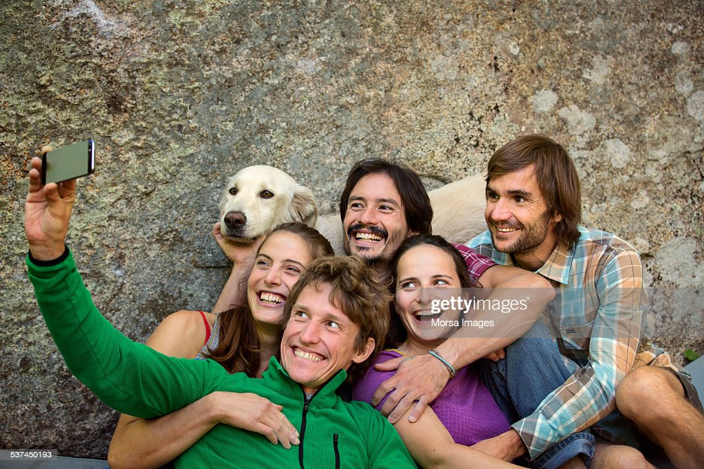 Friends taking selfie with dog against rock : Stock Photo