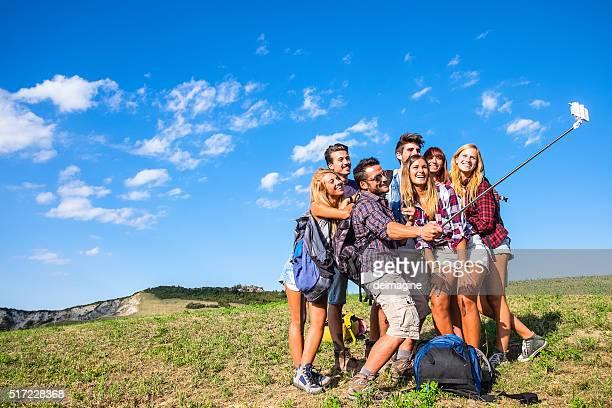 Friends taking selfie with selfie stick