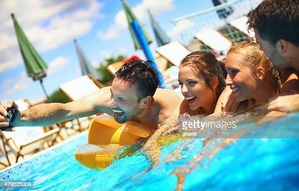 Friends taking selfies in swimming pool.