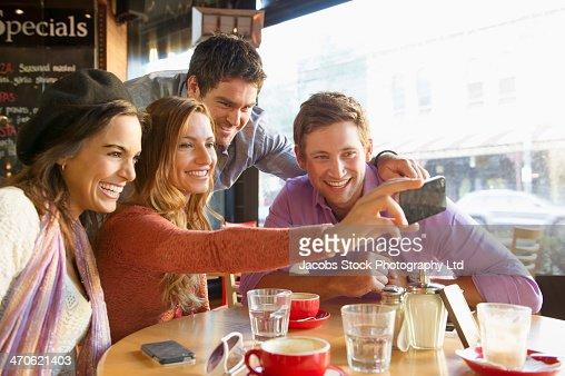 Friends taking self-portrait in cafe