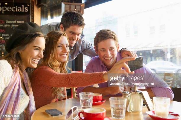 Friends taking self-portrait in cafe