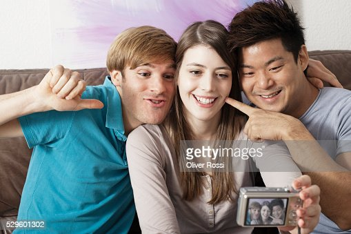 Friends taking self-portrait photo on couch : Stockfoto