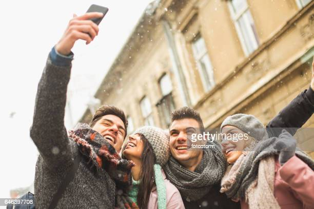 Friends taking self-portrait with camera phone outdoors