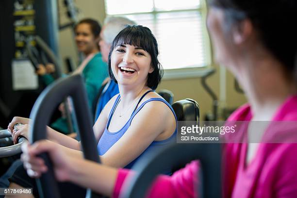 Friends talk as they exercise on stationary bicycle