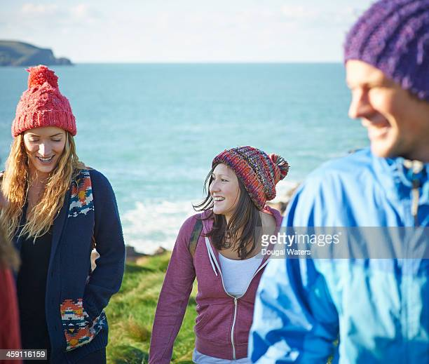 Friends talk as they walk along coastline.