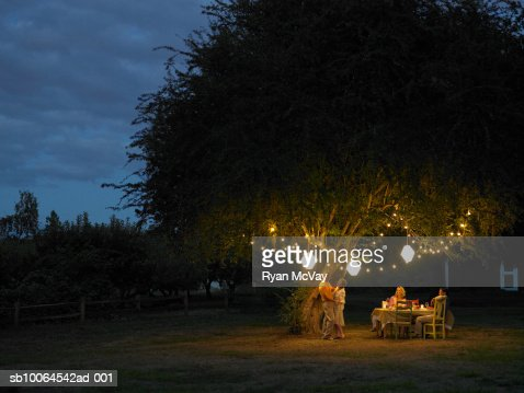 Friends talking and dancing in yard at dusk : Stock Photo