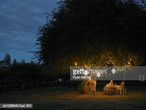 Friends talking and dancing in yard at dusk : Foto de stock