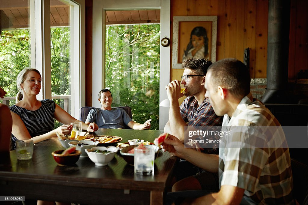 Friends talking and laughing at table in cabin : Stock Photo