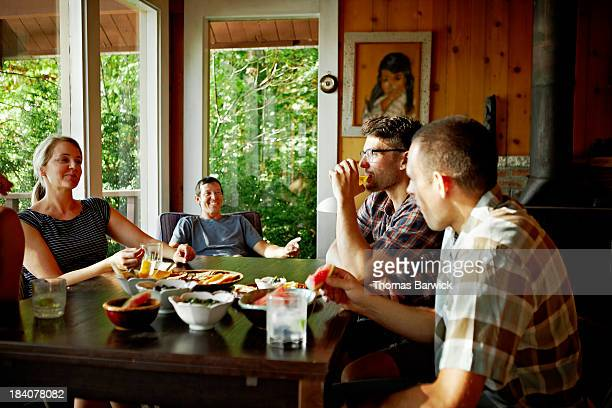 Friends talking and laughing at table in cabin