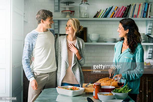 Friends talking and preparing food in kitchen