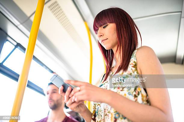 Friends talking and using the smartphone inside a bus