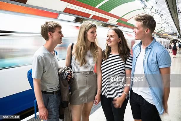 friends talking and waiting the train on a subway station