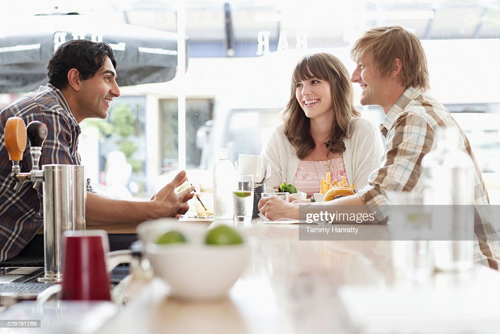 Friends talking at bar counter : Stock Photo