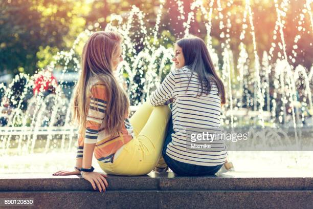 Friends talking at the fountains in the park