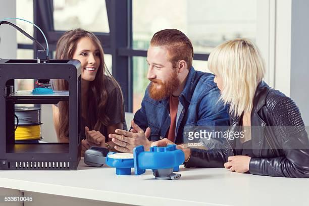 Friends talking in 3D printer office