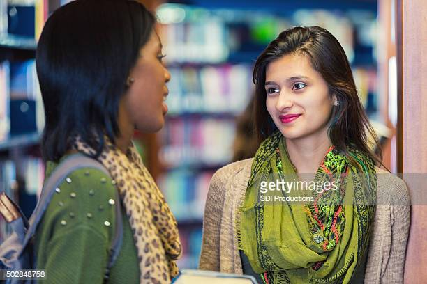 Friends talking in modern public library