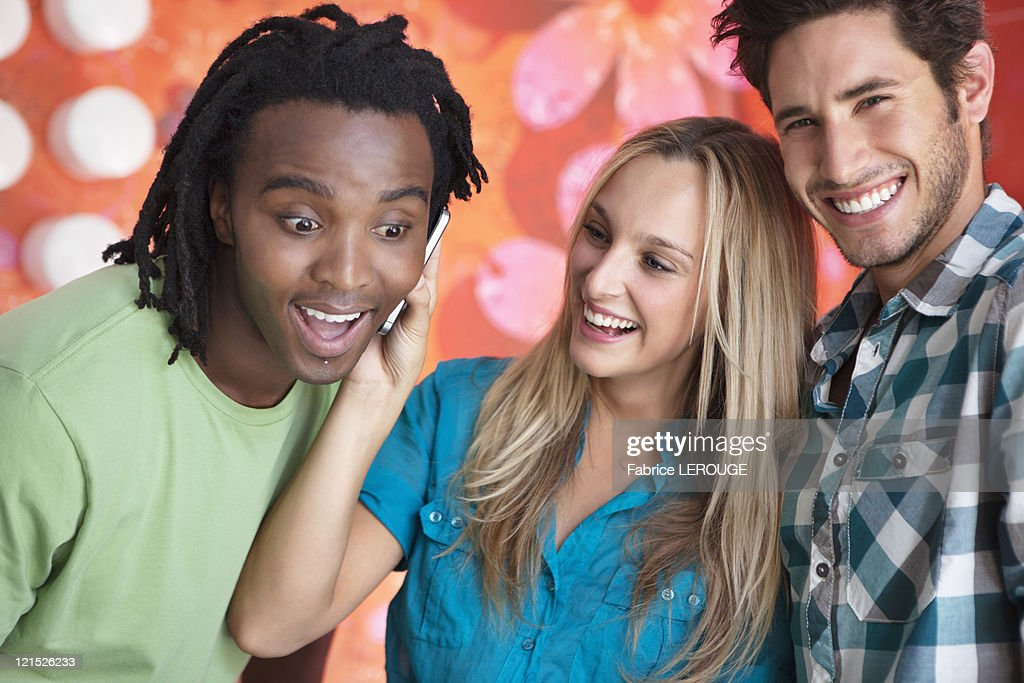 Friends talking on a mobile phone in a bar : Stock Photo