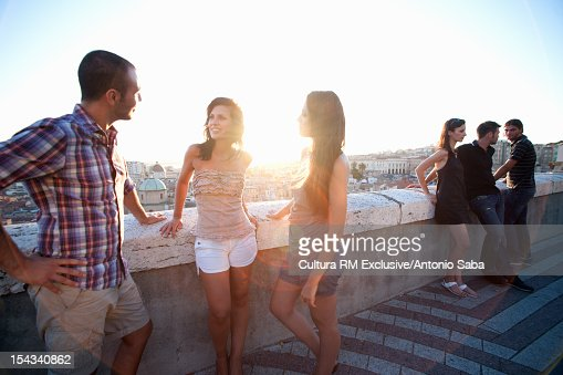 Friends talking on balcony at sunset