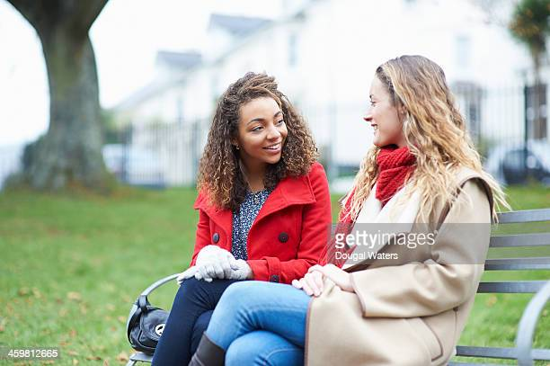 Friends talking on park bench.