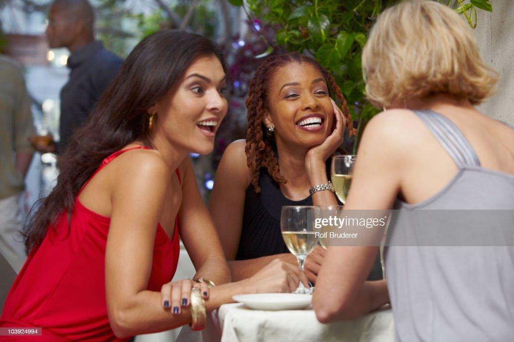 Friends talking over dinner in restaurant