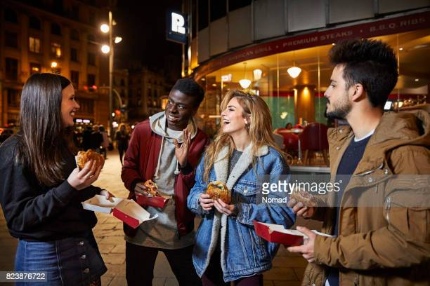 Friends talking while having burgers at night