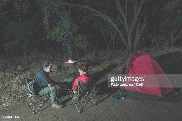 Friends Talking While Sitting By Fire Pit And Tent At Night