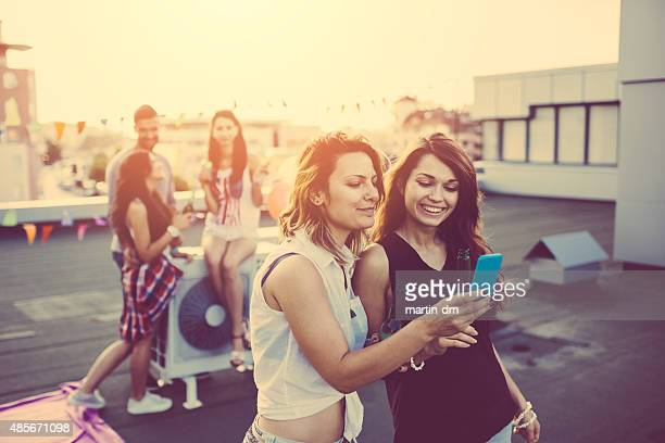 Friends texting on smartphone and drinking beer on a party