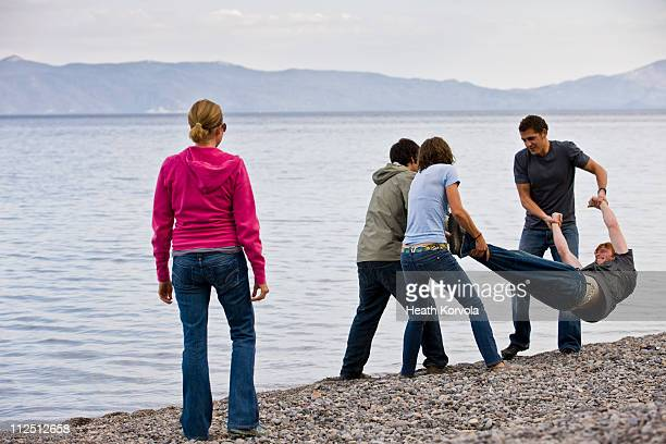 Friends throwing man in lake.